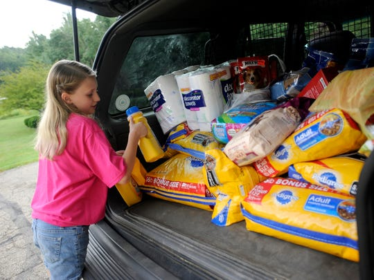 Allison Lutz, 10, helps unload dog food, treats, cleaning supplies and more from her mother's car at the Ross County Humane Society on Wednesday. Allison was asking for donations to the shelter in lieu of birthday gifts for her tenth birthday this year.
