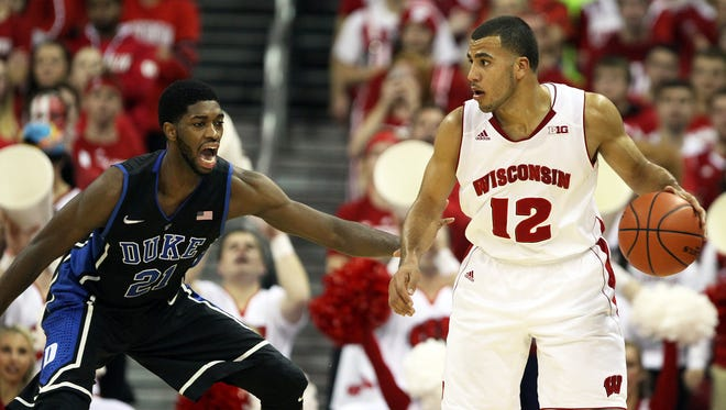 Wisconsin Badgers guard Traevon Jackson (12) looks to pass as Duke Blue Devils forward Amile Jefferson (21) defends at the Kohl Center in Madison, Wisc., on Dec. 3, 2014. Duke defeated Wisconsin 80-70.