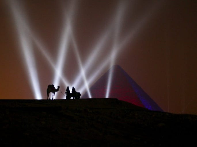 Two Egyptian men and a camel stand on a hill overlooking one of the Giza Pyramids during a New Year's Eve fireworks display near Cairo, Egypt at midnight on Friday, Jan. 1, 2016.