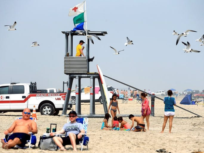 GABE HERNANDEZ/CALLER-TIMES A lifeguard keeps watch as beachgoers enjoy the day during spring break Thursday, March 17, 2016, at South Packery Channel in Corpus Christi.