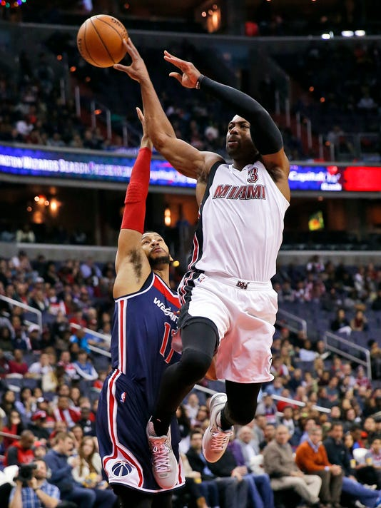 Miami Heat guard Dwyane Wade (3) passes the ball over Washington Wizards guard Garrett Temple (17) in the first half of an NBA basketball game, Sunday, Jan. 3, 2016, in Washington. (AP Photo/Alex Brandon)