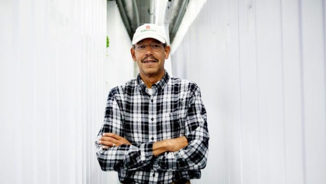 Brian Harris, founder of Green Collar Farms, poses for a photo at the farm in Grand Rapids on Thursday, Aug. 31, 2017. The farm is in a 340 square foot storage container and uses hydroponics to grow greens without soil. (Neil Blake | MLive.com)