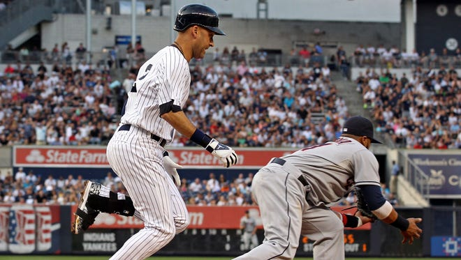Derek Jeter is safe at first base in front of  Indians first baseman Carlos Santana at Yankee Stadium. The hit was changed to an error by Santana.