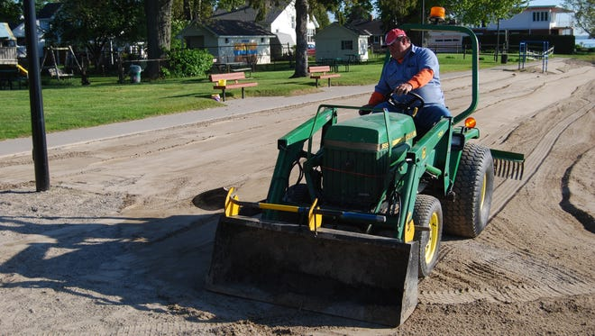 Rick Hupcik of the Marine City Department of Public Works uses a tractor to groom the city beach.