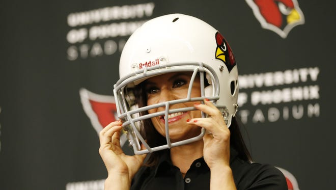 Dr. Jen Welter puts a helmet on after being introduced during a press conference at the team's training facility in Tempe July 28, 2015. She is the first female coach in the NFL and will be a Cardinals coaching intern for training camp and the preseason.