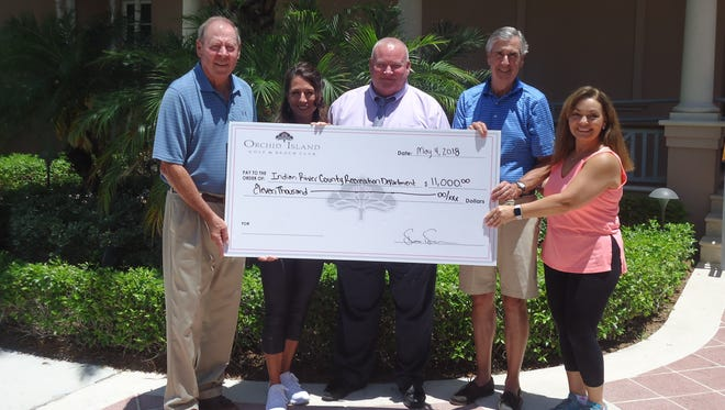 Indian River County Recreation Department Director Mike Redstone, center, accepts a donation of $11,000 from Orchid Island representatives Jim Gaede, left, Denise Duda,   Bruce Morrison  and Micki Weilbaker.