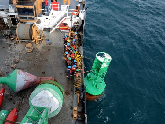 Crew members reach out to retrieve a buoy Sunday, Dec. 20, during the annual family buoy swap on board the USCGC Hollyhock.