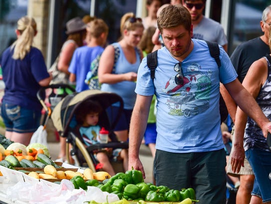 A shopper stops to check out a table of fresh vegetables