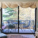The living room offers a view of the balcony deck with a tapestry of trees behind.