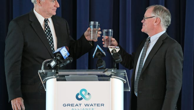 Milwaukee Mayor Tom Barrett (left) and Waukesha Mayor Shawn Reilly share a toast with glasses of Milwaukee water in October when they announced a 40-year water service agreement. The Milwaukee Common Council on Tuesday approved the agreement to sell Lake Michigan water to Waukesha.