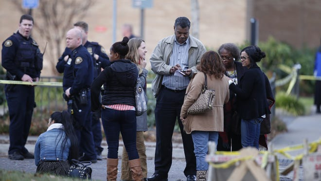 Officials speak to people at the scene of a shooting at Rosemary Anderson High School in North Portland  Friday, Dec. 12, 2014. A shooter wounded two boys and a girl outside the high school Friday in what may be a gang-related attack, police said.