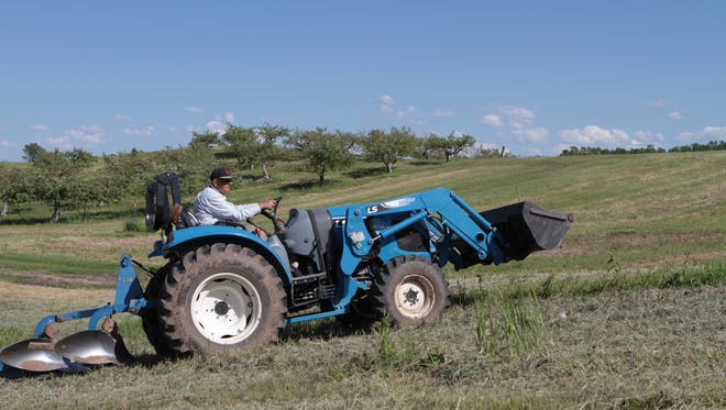 Munir Bahai, an owner at The Apple Farm in Victor, drives a tractor through one of the fields on the 140-acre property.