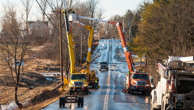 Crews work to erect a utility pole on a closed section of Spear Street between Barstow Road and Webster Road in Shelburne on Wednesday, January 11, 2017