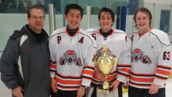 Big North hockey tournament director Cory Robinson presented the Silver Cup trophy to Tenafly/Cresskill captains, from left, Andy Chang, Kyle Picinic and Matt Brown on Friday.
