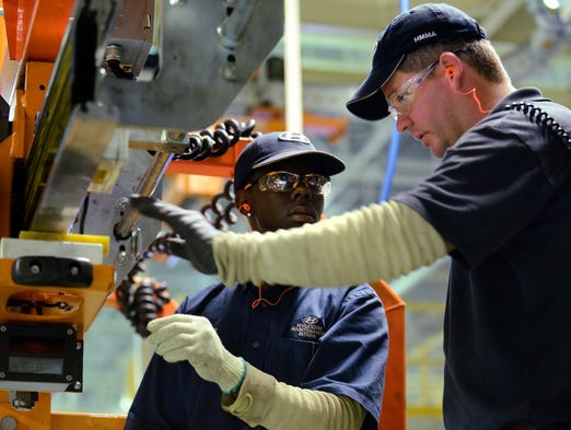 Trenholm State Technical College student Darien Fails, left, is instructed by Ben Rieves in the stamping shop at Hyundai Motor Manufacturing in Montgomery, Ala. on Friday August 15, 2014 as part of a student hands-on program at the plant.