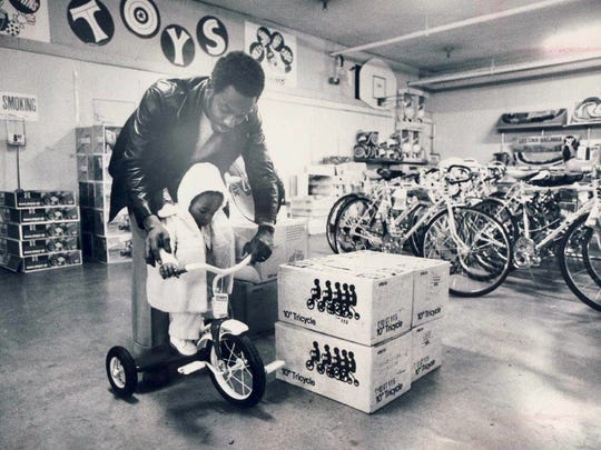 Essex Bosan helps his one-year-old daughter, Kisha, try out a tricycle Dec. 4, 1974 in the toy department at Grant's department store at the River City Mall/4th Street in downtown Louisville.