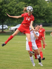 Canton's Mary Galm jumps up to head the ball away from