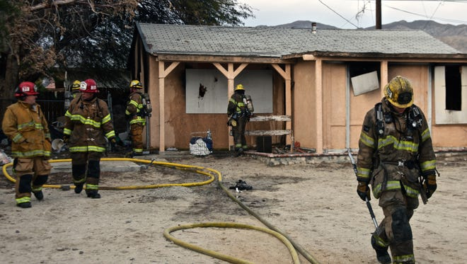 Firefighters leave the scene after containing a blaze at an unoccupied home near the corner of Palm Drive and Hacienda Avenue in Desert Hot Springs.