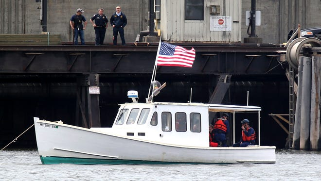 In this May 15, 2013 photo, protesters piloting the lobster boat Henry David T.,  attempt to block delivery of coal to the Brayton Point Power Station in Somerset, Mass.