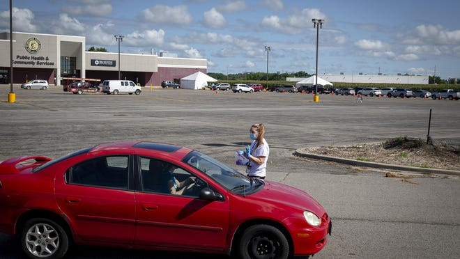 Hannah Turley, with SIU Medicine, walks the line of cars that snakes through the parking lot of the Sangamon County Department of Health in Springfield as she gathers an information sheet that is placed in a plastic bag as people queue in line for COVID-19 testing by SIU Medicine on Aug. 4.