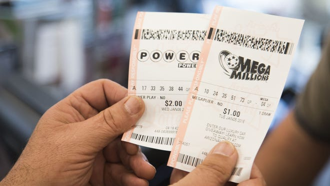 Jason Shaw (R) hands Bob Rossi (L) his lottery tickets as the Powerball sits at $400 million at a Chevron gas station on Jan. 4, 2016, in Phoenix, Ariz.