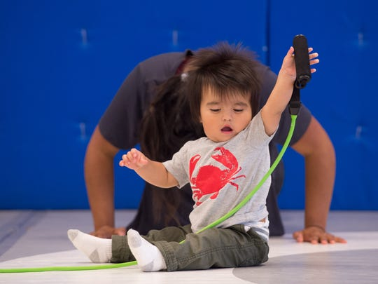 Deanna Cortez's son Tobias (1) of Dover plays with a work out band during the MOMentum fitness Delaware fitness class at Delaware Combat Sports in Dover.