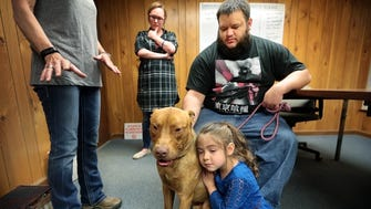 Cindy McCowan (left) talks about the history of the animal while Iraq veteran Quintus Price tries to decide if Huck is the right dog for him during a short introductory meeting in an office off Summer Ave. In the meantime, Lily Price develops her own opinion about Huck, who is a prospective candidate for special training to become a PTSD dog to help Quintus cope with issues stemming from his service in the Army.