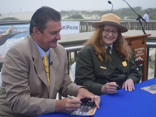 Jim Cochrane and Assateague Island Superintendent Deborah Darden sign programs for visitors clamoring for the first edition stamps. Cochrane visited Assateague for the launch because the United States Postal Service wanted to celebrate the beach park at the start of the summer.
