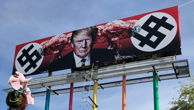 A billboard sign depicting President Donald Trump's face next to explosions and dollar signs created with typography imitating Nazi swastikas went up in downtown Phoenix on March 17, 2017.