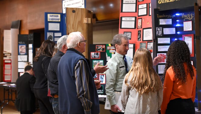 History professor Dan Feller, center, judges exhibits during East Tennessee History Day at the University of Tennessee on Friday, March 6, 2015. About 370 middle and high school students participated by entering exhibits, papers, web sites, documentaries, and live performances.