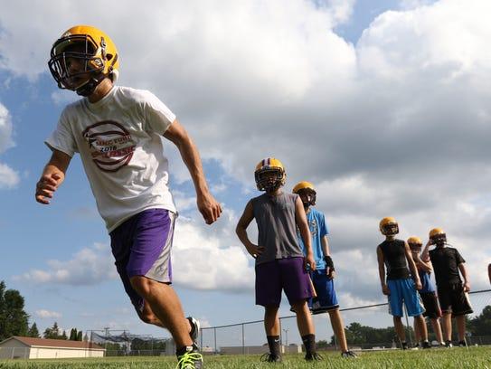 A Pittsville High football player runs a sprint during