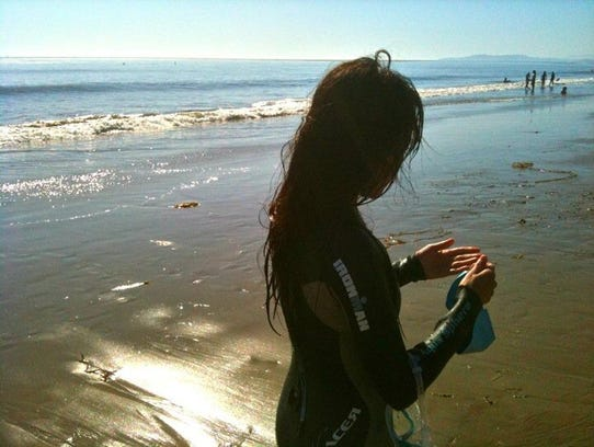 Kyung Lee emerges from an ocean swim off Carpinteria