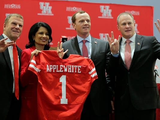 University of Houston Board of Regent Chairman Tillman Fertitta, left, school President Renu Khator, second from left, and Vice President of Athletics Hunter Yurachek, right, gesture during a press conference to introduce new NCAA college football coach Major Applewhite, second from right, in Houston, Monday, Dec. 12, 2016.( James Nielsen/Houston Chronicle via AP)