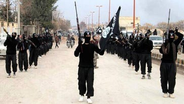 FILE - This undated file image posted on a militant website on Tuesday, Jan. 14, 2014 shows fighters from the al-Qaida linked Islamic State of Iraq and the Levant (ISIL) marching in Raqqa, Syria.