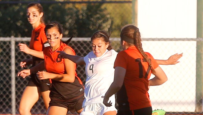 Farmington's McKenzie Coleman, center, scores a goal on Oct. 13 against Aztec at Hutchison Stadium in Farmington.