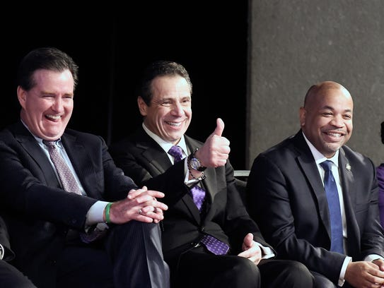 New York Gov. Andrew Cuomo, center, is flanked by Senate