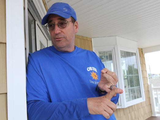 Jerry Alloco of Paramus, who owns a second home on West Osprey Way in Ocean Beach III in Toms River, talks about the community's board of directors decision to prohibit exterior work in the 950-home community from June 15 through Labor Day at his home Wednesday May 28, 2014. Many homeowners have just started to raise their homes and rebuild after Sandy and now they are faced with another nearly 3-month delay.