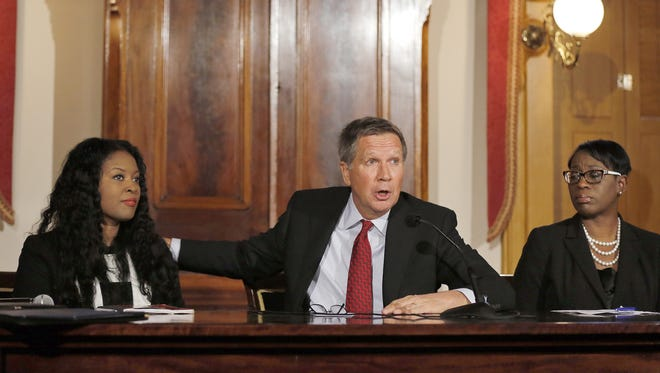 Gov. John Kasich (center) announces a new task force Friday to improve police-community relations. With him are state Rep. Alicia Reece, who introduced a bill to require BB guns to be bright in colors, and state Sen. Nina Turner.