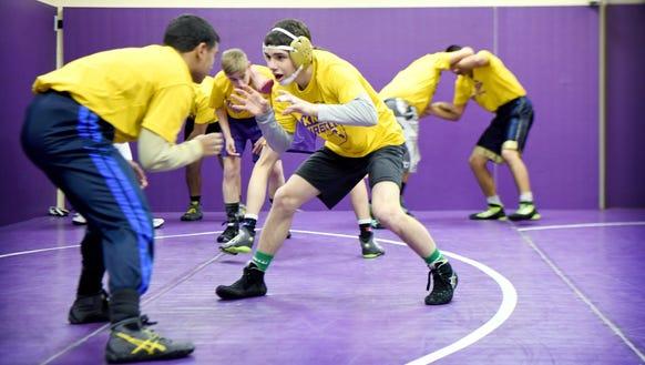 North Henderson's Josh Blatt, right, wrestles with