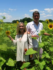 Camille and Don Hathaway in sunflower field.