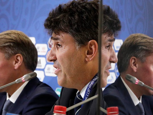 Massimo Busacca, FIFA head of refereeing, centre, and Alexey Sorokin, 2018 FIFA World Cup Russia local organising committee CEO, are reflected in a TV screen, right, during half–time press conference following the group stage of the Confederations Cup in St.Petersburg, Russia, Monday, June 26, 2017. (AP Photo/Dmitri Lovetsky)