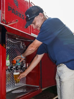 Parks Department employee Tyler Devinger taps a glass of Sprecher beer during the Milwaukee County Parks Traveling Beer Garden tour in Grant Park on Thursday, June 28, 2018. The Traveling Beer Garden features craft beer, gourmet sodas, hard root beer, hard ginger beer, and other refreshments from Sprecher Brewing.