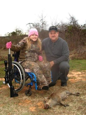 Peydan Brown, 9, is all smiles after shooting a hog as part of a Dream Hunt Foundation adventure that was hosted by the Bossier Sheriff's Office. Chief Deputy Charles Owens of the Bossier Sheriff's Office assisted with the hunt.