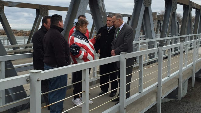U.S. Charles Schumer, right, talks on the Irondequoit Bay Outlet Bridge with Fran Beth of Marge's Lakeside Inn and other nearby business owners last December, as Schumer called for a federal study of upgrades to the bridge.