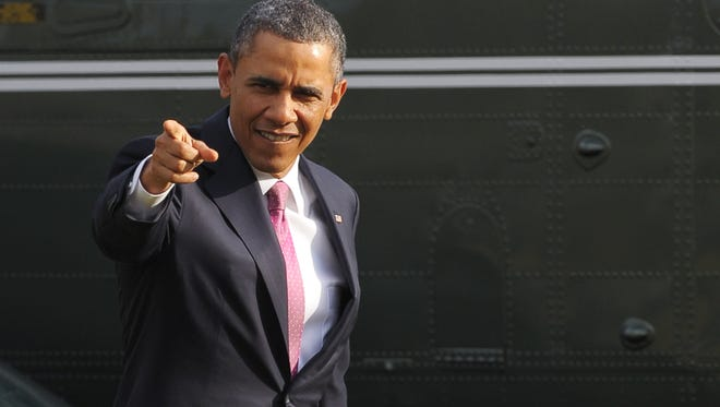 President Obama points to a person viewing his Marine One return on March 5, 2013 on the South Lawn of the White House.