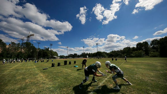Port Washington High School Varsity Assistant Football Coach Dave Gall looks on as Tyler Beach squares off against Nolan Fullington (right) during the teams practice at the school Friday, Aug. 5, 2016, in Port Washington, Wisconsin.