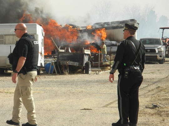 Officers with the New Mexico State Police survey flames at an Artesia home following the spread of a grass fire on Feb 28 by high winds in the area.