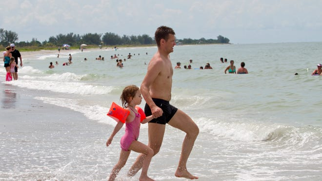 Dirk Hauser, of Zurich, Switzerland, and his daughter, Livia, 4, romp at Bowman's Beach on Sanibel Island. A report found that the beach no longer exceeds EPA bacteria standards.