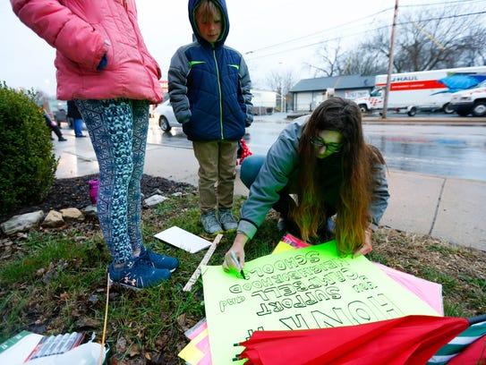 Caroline Murski makes a sign to protest the proposal