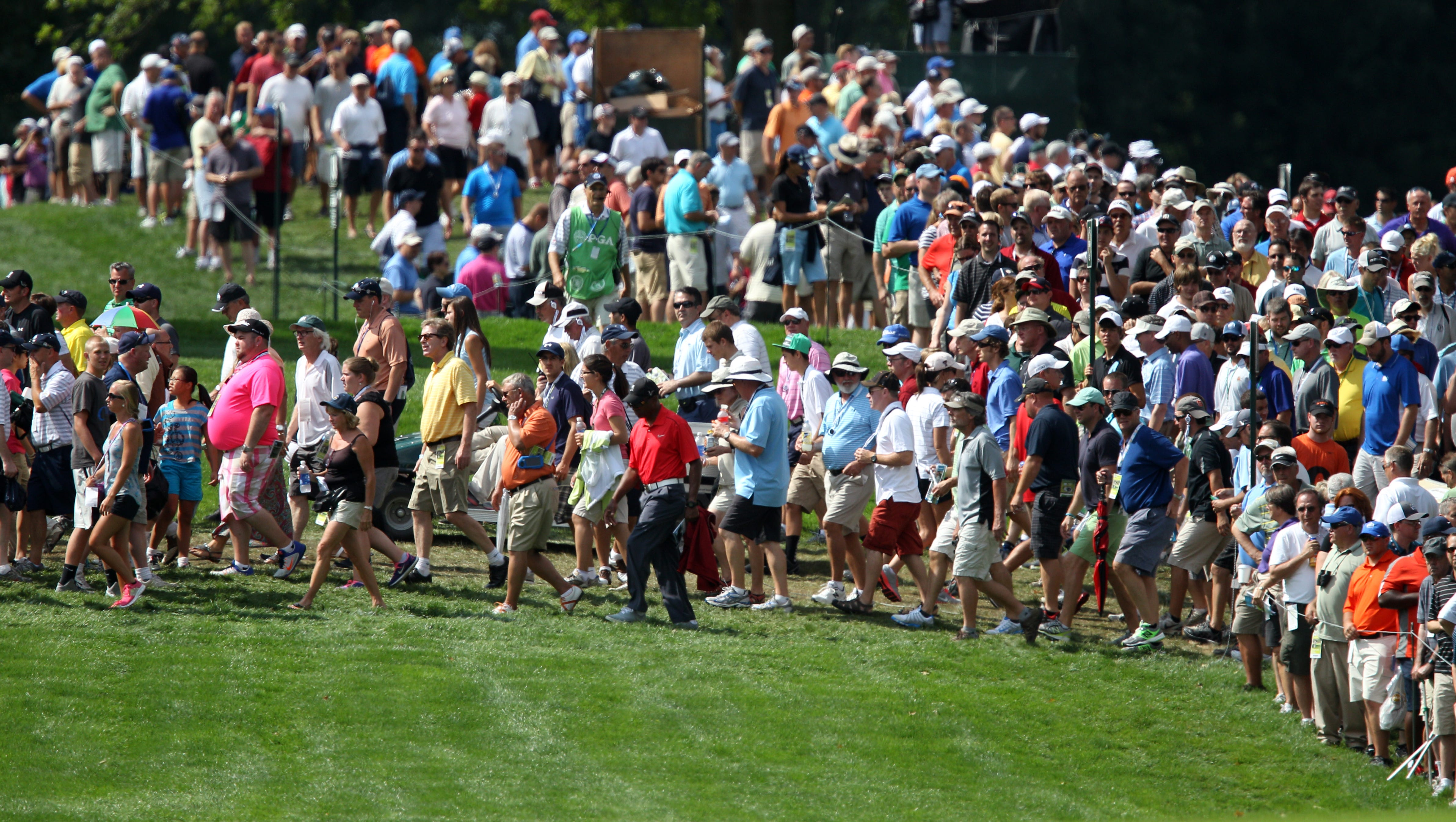 Fans cross 18 following Tiger woods during the first round of the 95th PGA Championship at Oak Hill in Pittsford, NY August 8, 2013.